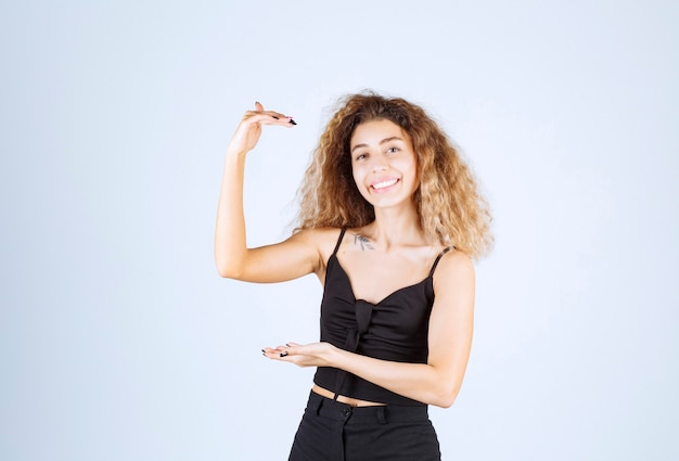 Blondie woman showing the size of an object.