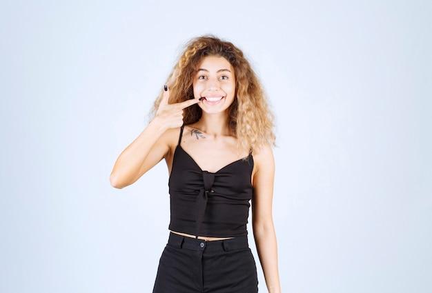 긍정적이고 웃는 포즈를주는 곱슬 머리를 가진 블론디 여자.
