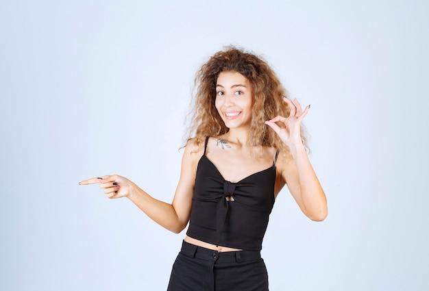 좋은 손 기호를 보여주는 곱슬 머리를 가진 금발 여자.