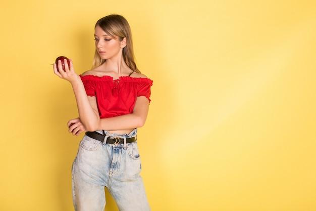 Красивый молодой кавказский портрет девушки blondie красоты с яблоком на желтой стене