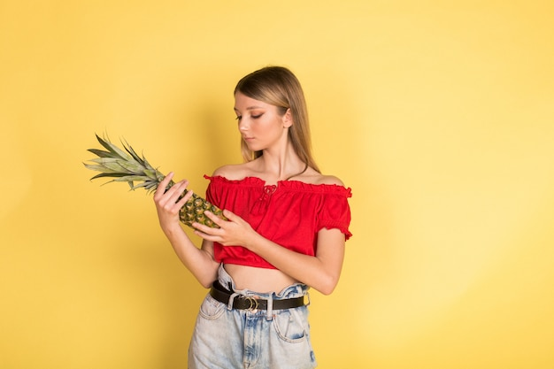 Красивый молодой кавказский портрет девушки blondie красоты на желтой стене с ананасом