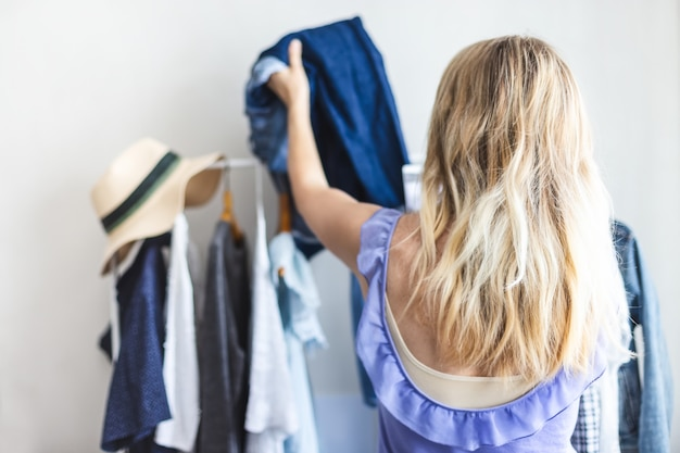 Blondy girl near a wardrobe with clothes