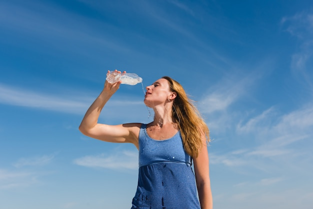Blondy thirsty woman drinking water