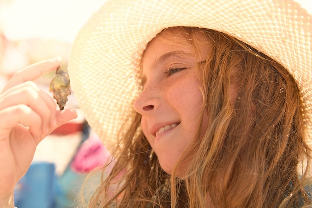 Blonk kid girl holding hermit crab