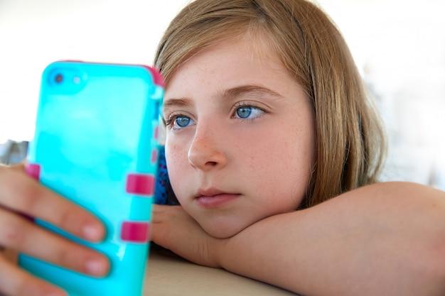 Blonk kid girl looking smartphone