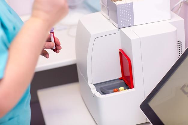 혈액 분석기. 의료 실험실의 실험실 조수는 혈액과 혈장이 있는 시험관을 손에 들고 분석을 하고 있습니다.
