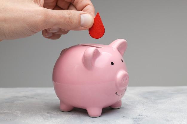 헌혈자. 한 남자가 손에 빨간 피 한 방울을 들고 기부금으로 돼지 저금통에 넣습니다. 회색 배경