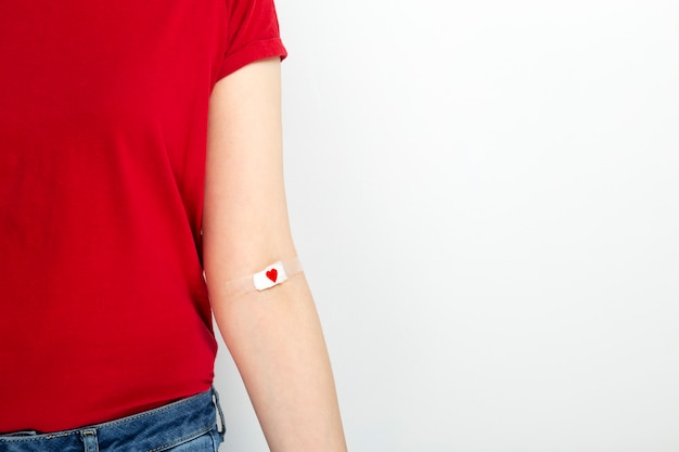 Blood donorship. young girl in red t-shirt hand taped with patch with red heart after giving blood on gray background.