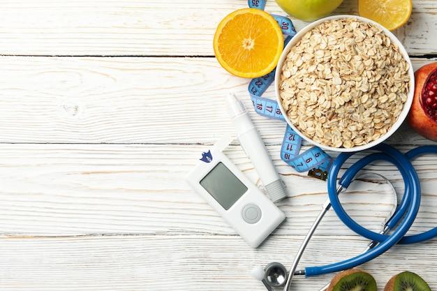 Глюкометр и диабетическая еда на деревянный стол