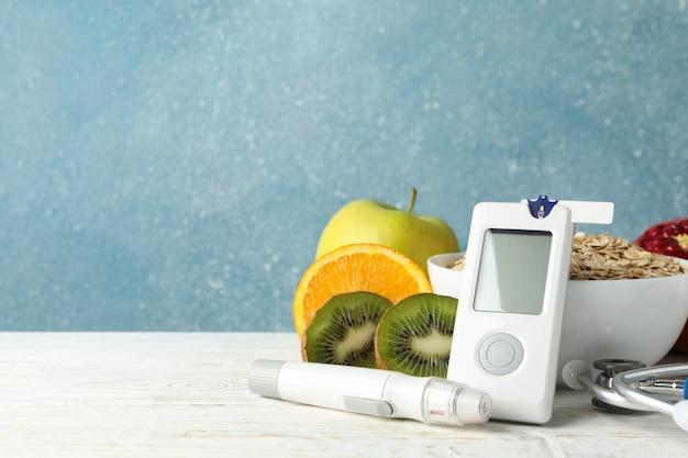 Измеритель уровня глюкозы в крови и диабетическая еда на деревянном столе