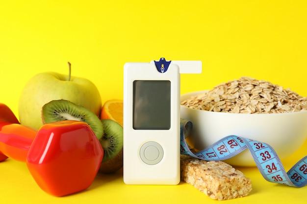 Глюкометр и диабетическая пища на желтом фоне