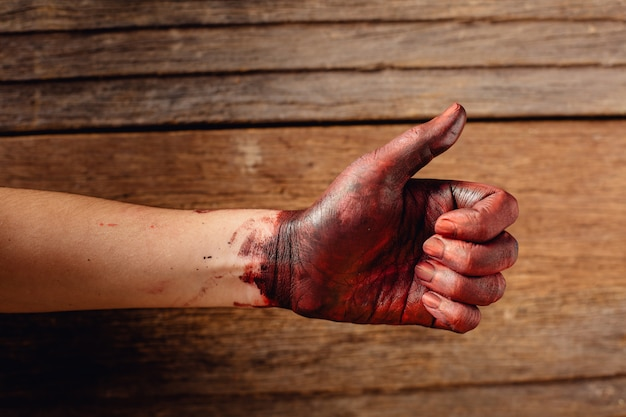 Blood on the hand with thumbs up on wooden