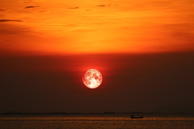 Blood moon on night sunset sky back horizon sea