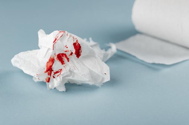 白い背景の上のティッシュペーパーの血。健康医療の概念。