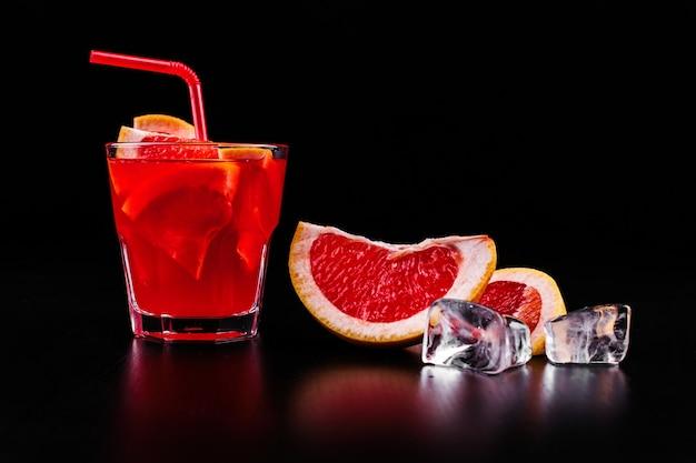 블러드 오렌지 진과 토닉 칵테일은 유리에 오렌지와 얼음 조각과 함께 제공