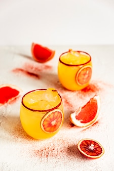 Коктейль «маргарита» из красного апельсина в старинном бокале с копченой паприкой по ободку, розовый грейпфрут.