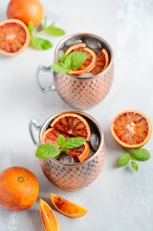 Blood orange moscow mule alcohol cocktail with fresh mint leaves and ice in copper mugs on a gray concrete background.
