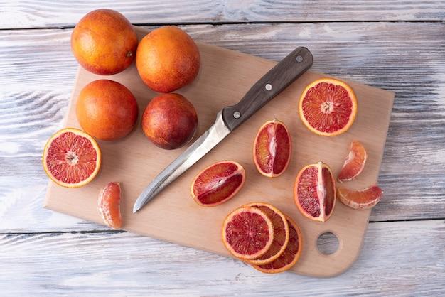 Дольки кровавого апельсина на разделочной доске с целыми цитрусовыми
