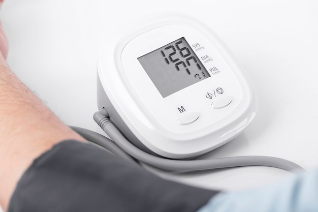 Blood pressure and heart rate machine working on white background close up