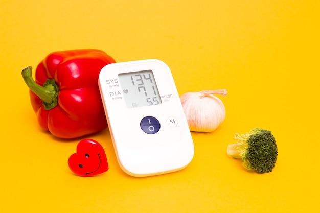 黄色の背景に血圧計と野菜