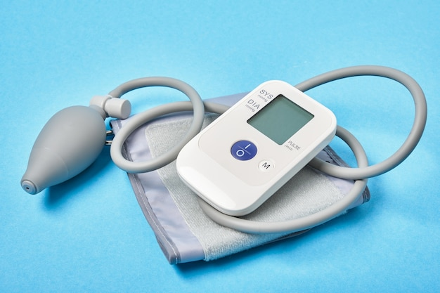 Blood pressure monitor on blue background copy space