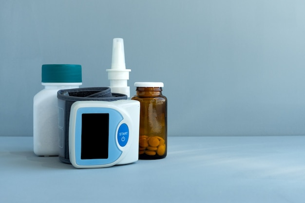 Blood pressure monitor, medications and pills on blue background. healthcare medical doctor concept. copy space.