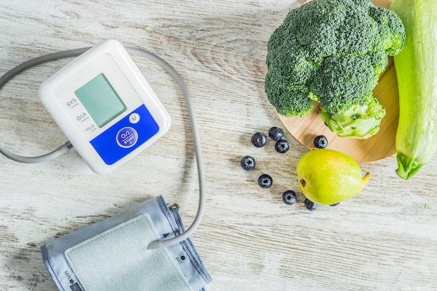 緑の果物と野菜のテーブルの隣のテーブルの血圧モニター