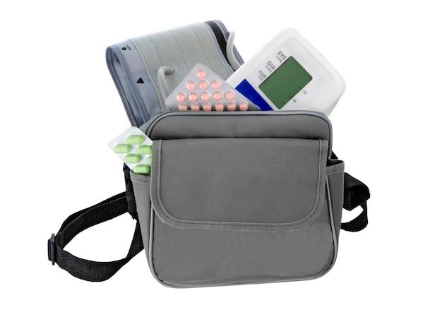 Монитор артериального давления, таблетки, сумка на белом. набор медицины. концепция здравоохранения.