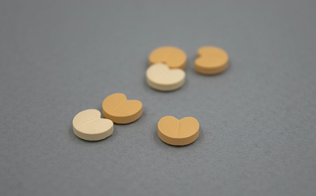 Blood pressure pills in heart form on grey background.