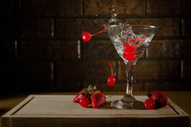 Blood-red cherries falling in the cocktail on a wooden board