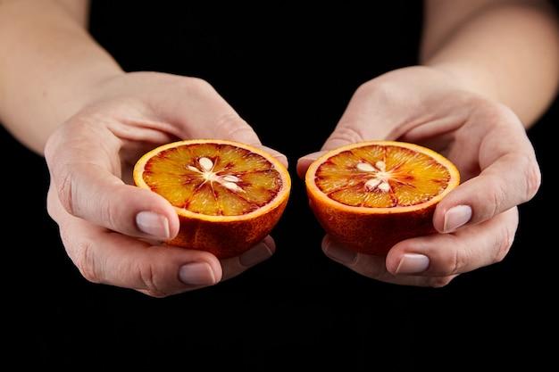Blood or red orange fruit halves in hands on black wall