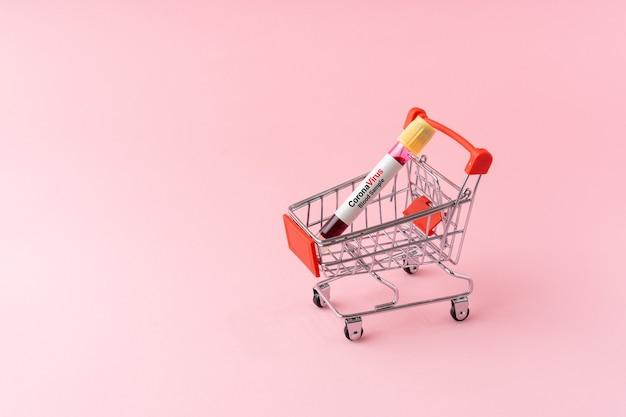 淡いピンクの背景のショッピングカートの血液サンプル真空管。