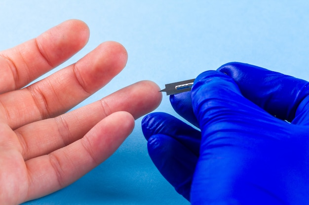 Blood sampling for analysis, piercing a finger with a scarifier