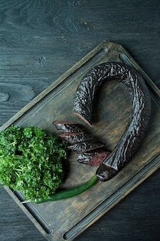 Blood sausage on a dark cutting board decorated with curly parsley.