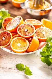 Кровь сицилийских апельсинов, нарезанных на белой тарелке со свежей мелиссой.