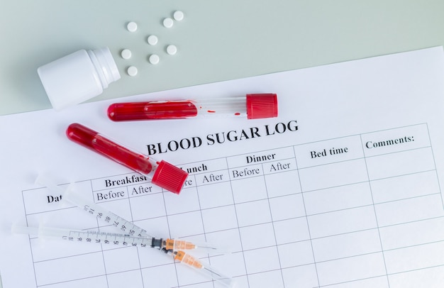 Blood sugar log with blood sample tubes, syringes and pills top view. world diabetes day, 14 november concept