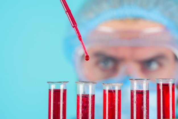 Blood test doctor in medical mask and glasses making research in laboratory male medical or