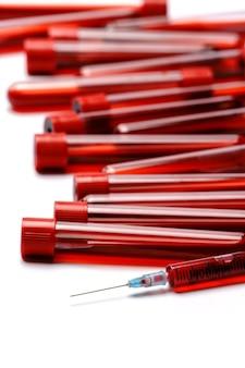 Пробирка крови с красной пробкой, изолированные на белом фоне.