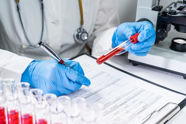 Пробирки для анализа крови. старший женский ученый, изучения пробирки в ее лаборатории дна тестирования