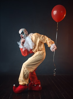 Bloody clown in carnival costume holds air balloon