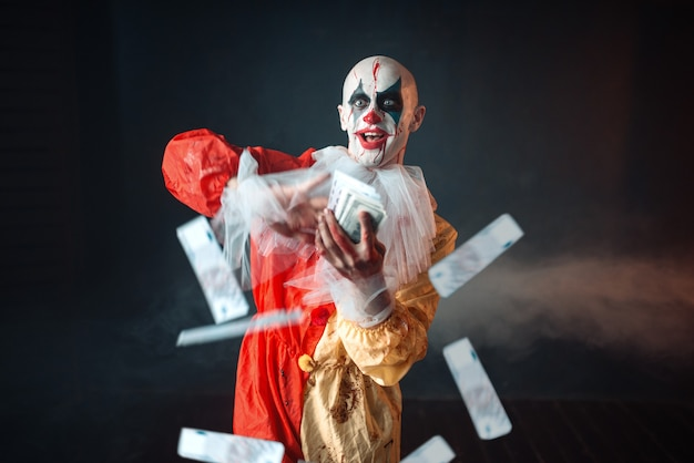 Bloody clown with crazy eyes holds fan of money