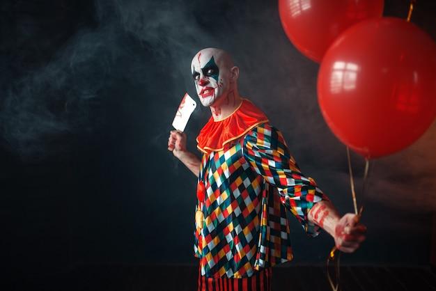 Кровавый клоун с мясорубкой держит воздушный шар