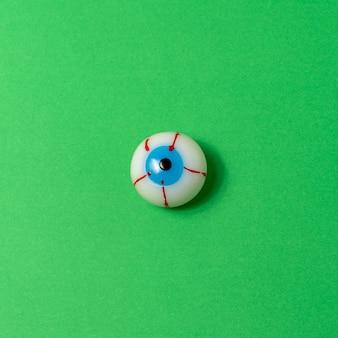 鮮やかな緑の背景に血まみれの眼球