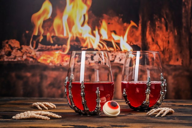 Bloody halloween party cocktail with bat. halloween cranberry punch over burning fireplace
