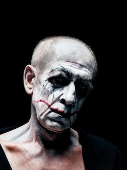血まみれのハロウィーンのテーマ:暗いスタジオの背景に狂ったマニアックな顔