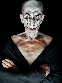 Тема кровавого хэллоуина: безумное лицо маньяка на темной студии