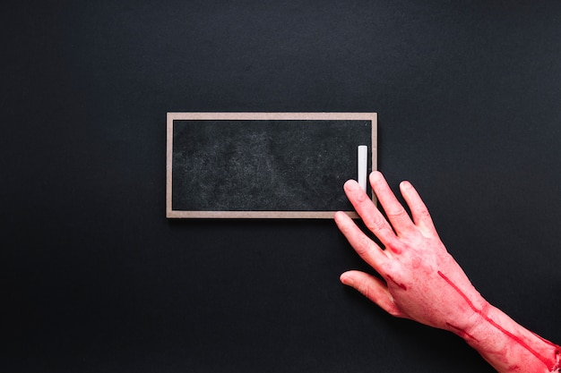 Bloody hand on chalkboard