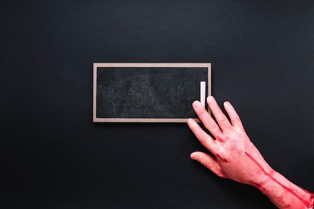 Bloody hand on chalkboard