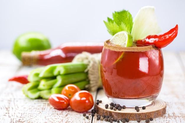 Кровавая мэри, красный напиток на основе водки, томатного сока, лимонного сока, сельдерея, гороха, вустерширского соуса, табаско и перца, на белой деревянной поверхности.