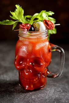 Bloody mary cocktail in glass skull with celery sticks, lime, and canned vegetables